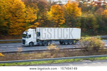 White lorry with conatainer on the road in an autumn scenery