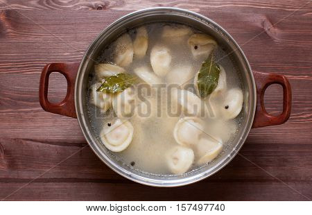 Dumplings in a pot on the wooden background