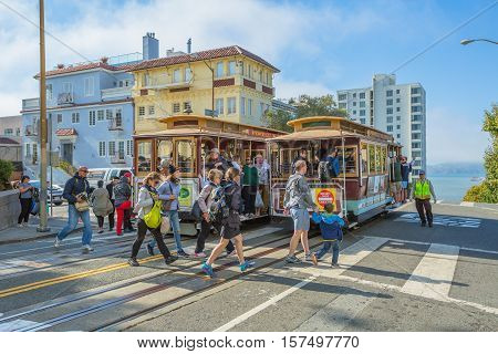 San Francisco, CA, USA - August 16, 2016: Two Cable Car of San Francisco, Powell-Hyde lines meet. Tourists crossing the intersection between Hyde and Lombard Street, popular touristic attraction.