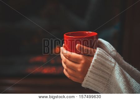 Girl In Sweater Holding A Cup Of Coffee Close-up On Background Of A Living Room With A Fireplace And