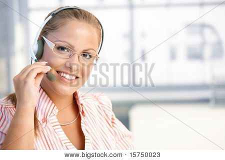 Pretty dispatcher working in office, using headset, smiling.?