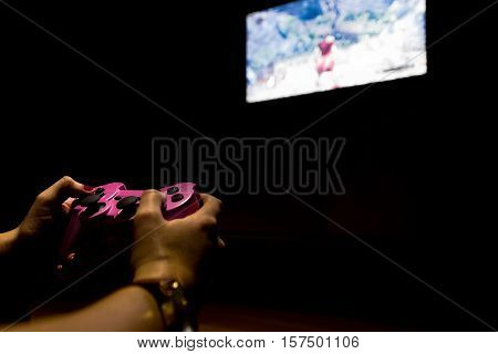 Girl with painted nails playing in a television screen with a game-pad.