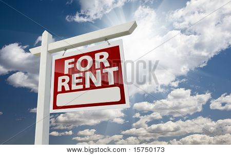 Right Facing For Rent Real Estate Sign Over Clouds and Sunny Sky with Room For Text.