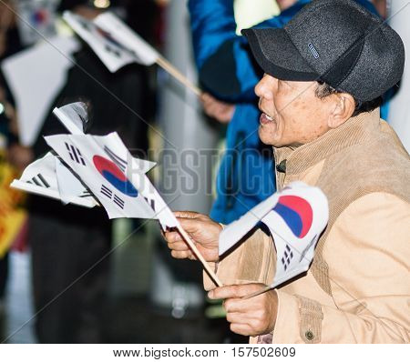 SEOUL, SOUTH KOREA, NOVEMBER 19,2016 Man waves Korean flag as part of a group of protesters outside Seoul Station rally against impeachment of President Park Geun-hye