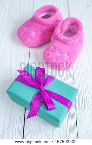 baby's bootees and gift box on wooden background.
