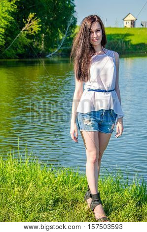 haired beautiful walks on the lake. girl in a summer forest near pond. Brunette standing near water. Girl in the forest near the pond.