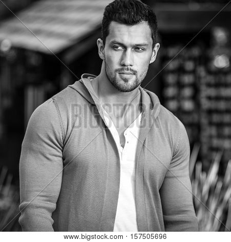 Black-white outdoor portrait of sporty handsome man in casual clothes against nature background.