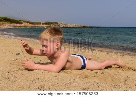 A boy playing on the seashore.  Family holiday.
