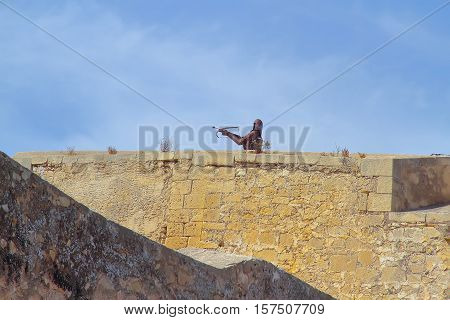 ALICANTE SPAIN - AUGUST 31: figure of an archer of metal on the rampart of the castle of santa barbara with sky as background. Picture taken on August 31 2016 in Alicante Spain