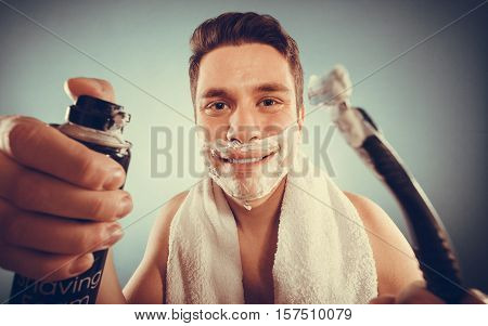 Handsome bearded young man with shaving cream foam can and razor preparing to shave. Skin care and hygiene. Instagram filter.
