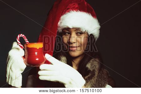 Christmas time concept. Mixed race teen girl wearing santa helper hat holding red mug with hot beverage and striped candy cane studio shot on dark