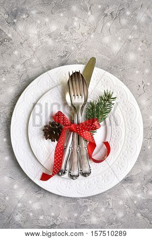 Christmas Table Place Setting With Christmas Pine Branches And Plates, Kine, Fork And Spoon.