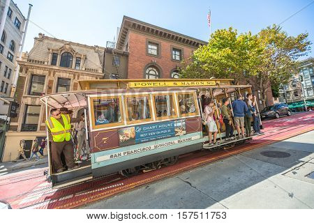 San Francisco, California, United States - August 17, 2016: Passengers enjoy a ride in the Cable Car Powell-Manson lines, while climbing on an uphill road in a sunny day.