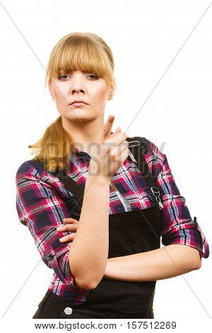 Gardening fahion concept. Attractive woman in pink check shirt and dungarees pointing at something angry face expression. Isolated background