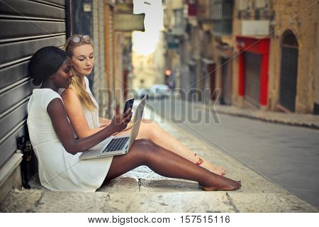 two friend in a street with laptop e smart phone
