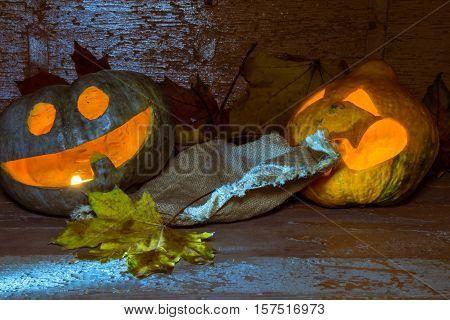 Yellow halloween pumpkin pulls a rug from under a green jack-o-lantern