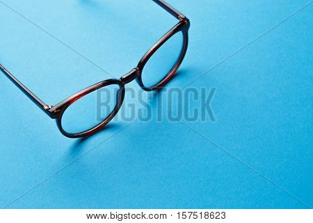 Brown spectacles on blue background