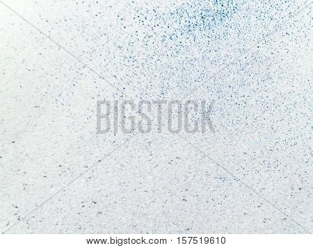 Abstract background in white with mottled blue, black and turquoise pattern.