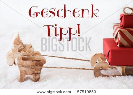 German Text Geschenk Tipp Means Gift Tip. Moose Is Drawing A Sled With Red Gifts Or Presents In Snow. Christmas Card For Seasons Greetings.