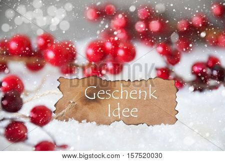 Burnt Label With German Text Geschenk Idee Means Gift Idea. Red Christmas Decoration On Snow. Cement Wall As Background With Bokeh Effect And Snowflakes. Card For Seasons Greetings