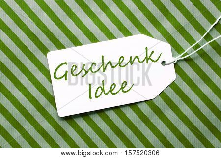 German Text Geschenk Idee Means Gift Idea. One Label On A Green Striped Wrapping Paper. Textured Background. Tag With Ribbon.