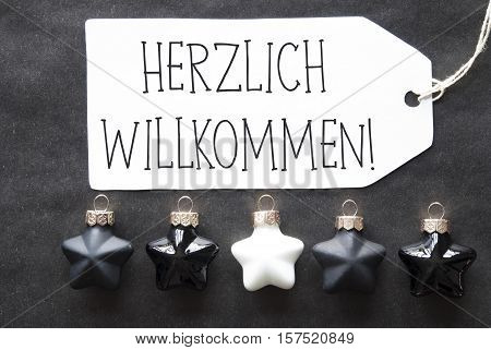 Label With German Text Herzlich Willkommen Means Welcome. Black And White Christmas Tree Balls On Black Paper Background. Christmas Decoration Or Texture. Flat Lay View