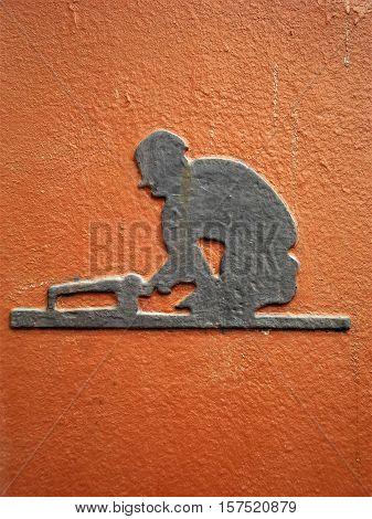 Silver colored metal stencil of a workman kneeling and working on a railway track on weathered orange background.