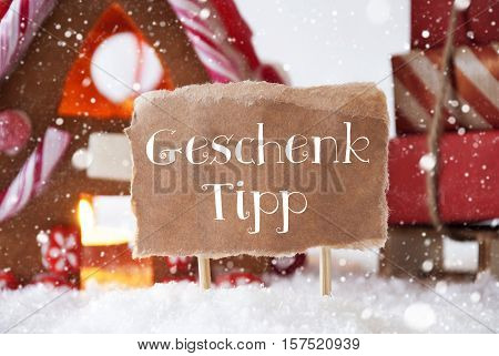 Label With German Geschenk Tipp Means Gift Tip. Gingerbread House In Snowy Scenery As Christmas Decoration. Sleigh With Christmas Gifts Or Presents And Snowflakes.