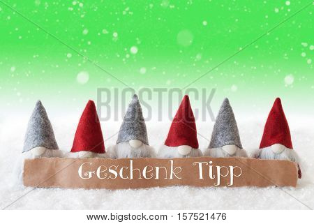 Label With German Text Geschenk Tipp Means Gift Tip. Christmas Greeting Card With Gnomes. Green Background With Snow And Snowflakes