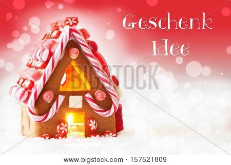 German Text Geschenk Idee Means Gift Idea. Gingerbread House In Snowy Scenery As Christmas Decoration. Candlelight For Romantic Atmosphere. Red Background With Bokeh Effect.