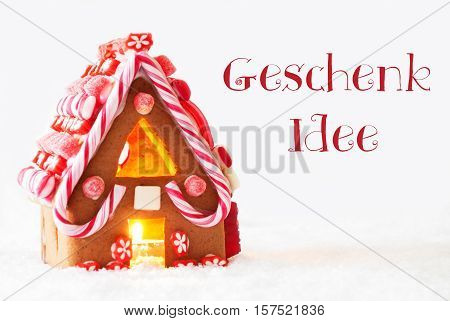 German Text Geschenk Idee Means Gift Idea. Gingerbread House In Snowy Scenery As Christmas Decoration With White Background. Candlelight For Romantic Atmosphere.