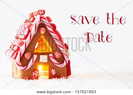 English Text Save The Date. Gingerbread House In Snowy Scenery As Christmas Decoration With White Background. Candlelight For Romantic Atmosphere.