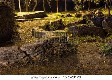 ancient old stones of ruined castle in the wood on a dark scary night.