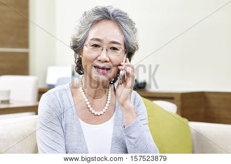 senior asian woman talking on cellphone appears to be disappointed upset and unhappy