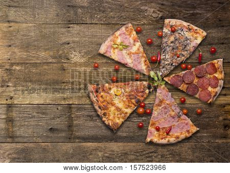Italian food - pizza on wooden table. Cherry tomato and hot peppers around