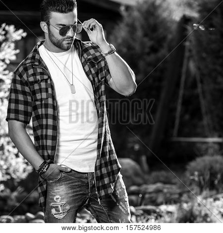 Black-white outdoor portrait of sporty stylish handsome man in casual clothes.