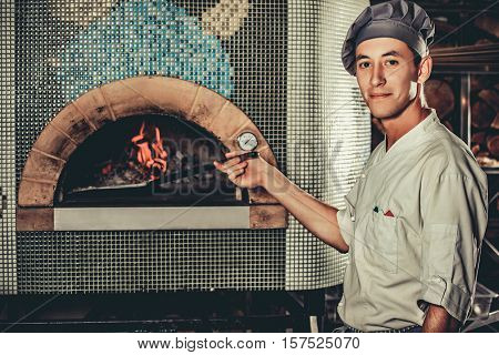 Young Italian chef in white uniform and hat in the kitchen interior. Man holding a shovel with a raw pizza and going to put it in a special oven.