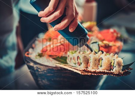 Chef in hotel or restaurant kitchen decorating tasty rolls with Japanese mayonnaise in bottle. Preparing sushi set. Only hands