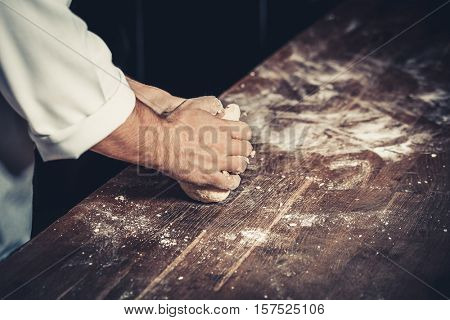 Professional chef kneads the dough for pizza on a wooden table. Flour around. Only hands, close up