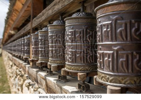 Buddhist prayer mani wall with prayer wheels in nepalese village on the Annapurna circuit trekking route, Nepal