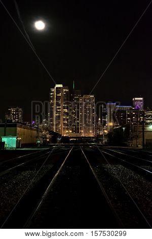 Moon over City Skyline and Train Tracks