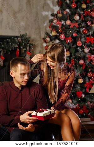 Couple in love and Christmas. Girlfriend gives her boyfriend a gift. Celebration for two. Family celebration.