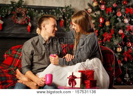 Loving couple and Christmas. Boyfriend and the girl sit on a couch and drinking a hot Christmas drink coffee. Girl barefoot. In the background a beautiful Christmas tree.
