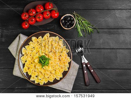 Farfalle Pasta Italian cuisine. Ingredients for pasta Farfalle cherry tomatoes fresh herbs thyme rosemary olives. Black wooden background. Farfalle Pasta on dark plate. Top view blank space