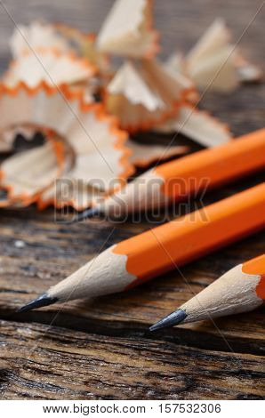 A low angle image of three yellow pencils and pencil shavings on a wooden table surface.
