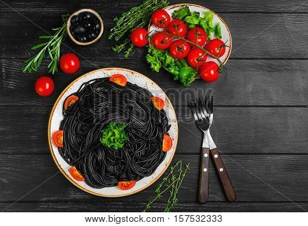 Spaghetti with ink of a cuttlefish. Ingredients for spaghetti with cuttlefish ink herbs thyme rosemary black olives lettuce. Spaghetti with cuttlefish ink decorated with cherry tomatoes. Top view.