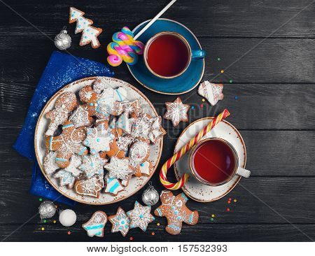 Christmas sweets baking gingerbread cookies on plate. Decorated for Christmas gingerbread cookies christmas bumps. Christmas cookies gingerbread on black table hot tea. New Year food. Top view.