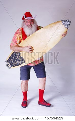 Surfing Santa. Rocker Santa. Causal Santa. Santa Claus Rocks Out with his surfboard as he plays it like an Air Guitar.