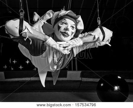 Circus air acrobat pose on ropes. Fine art black-white photo.