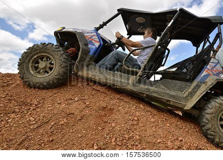 WATFORD CITY, NORTH DAKOTA, June 25, 2016: The unidentified helmet less man driving a Polaris 800 EPS Four Wheeler is a product of Polaris Industries,  an American manufacturer of snowmobiles, ATV, neighborhood electric vehicles, and tractor lookin things